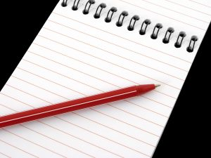 blank spiral notepad fragment with red pen